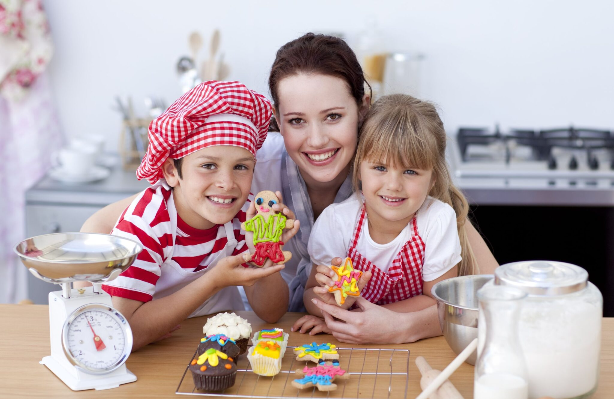 Nanny baking in the kitchen with young children