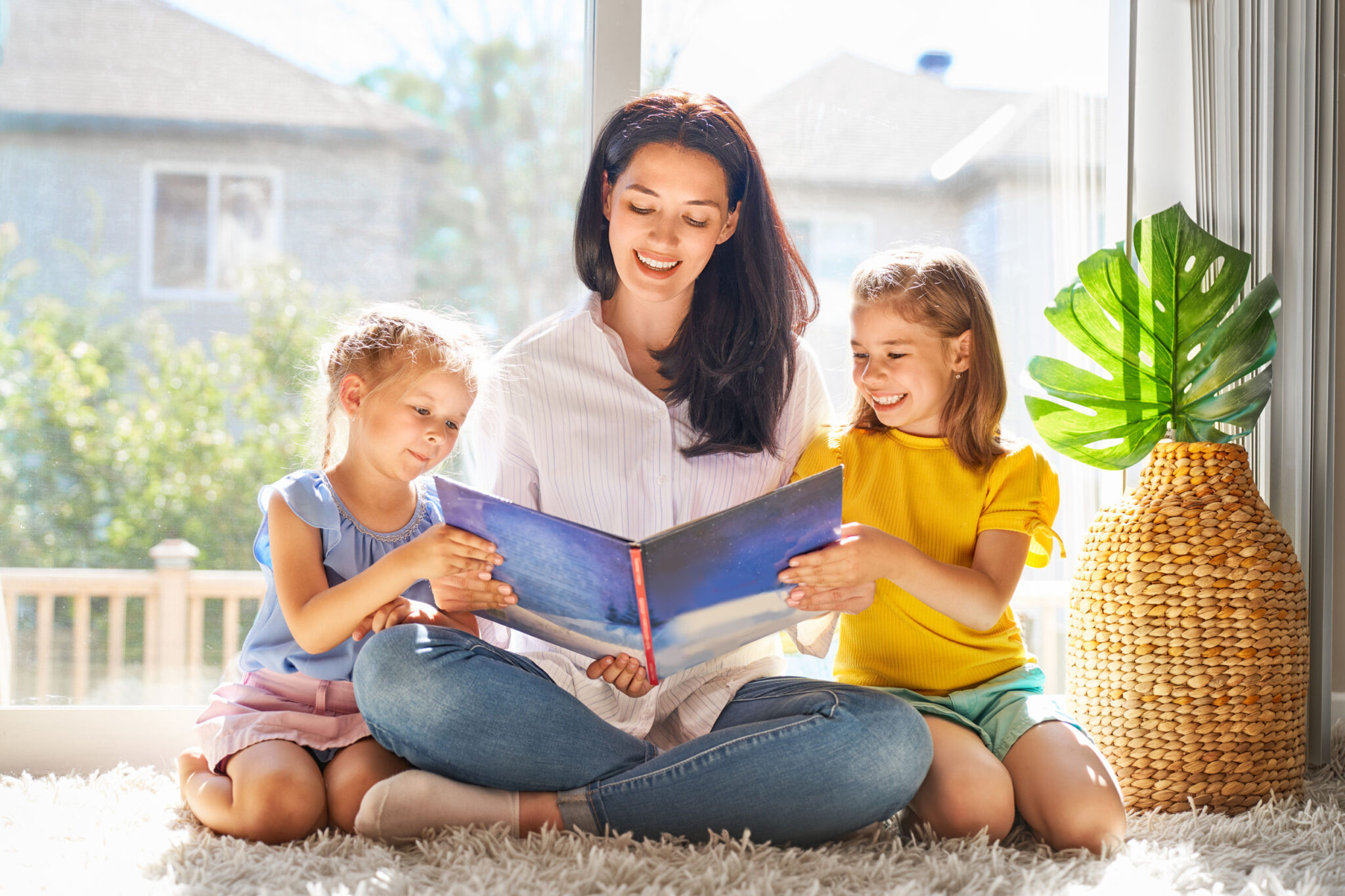 Bilingual Nanny reads book to 2 happy young children