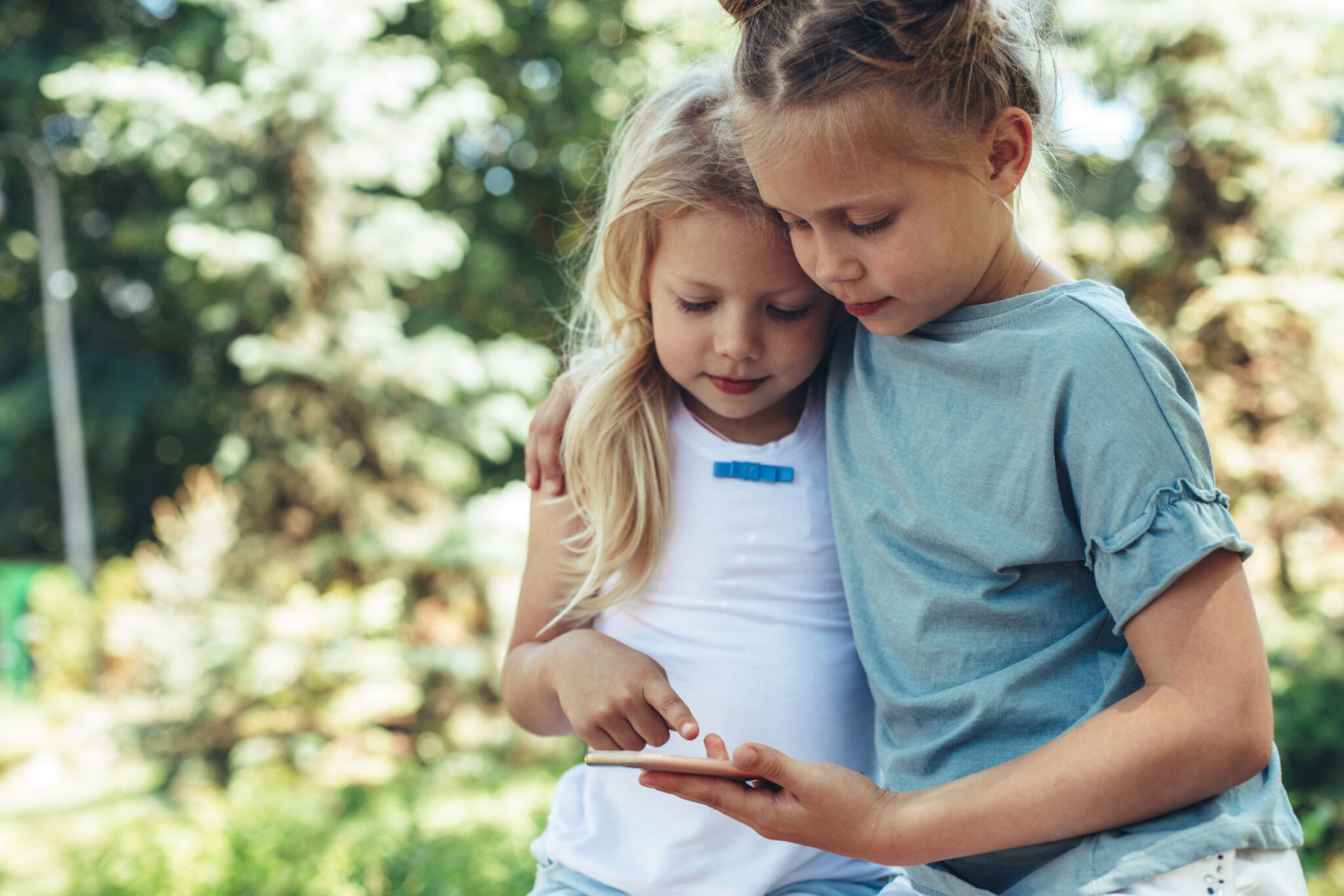 Waist up portrait of small girls standing in cuddles with phone in hands. They are playing games on smartphone peacefully. Copy space in left side