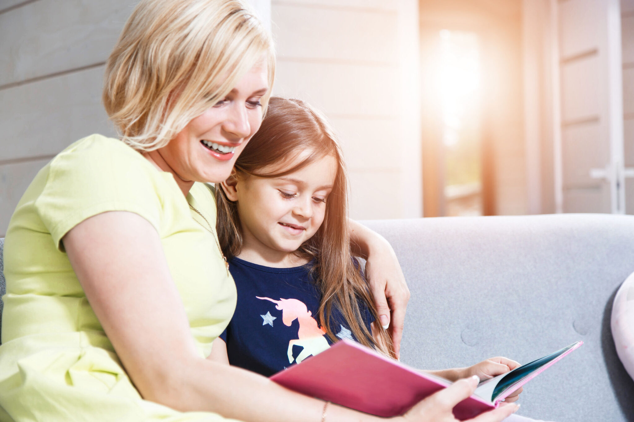 Blonde nanny shares book with young girl