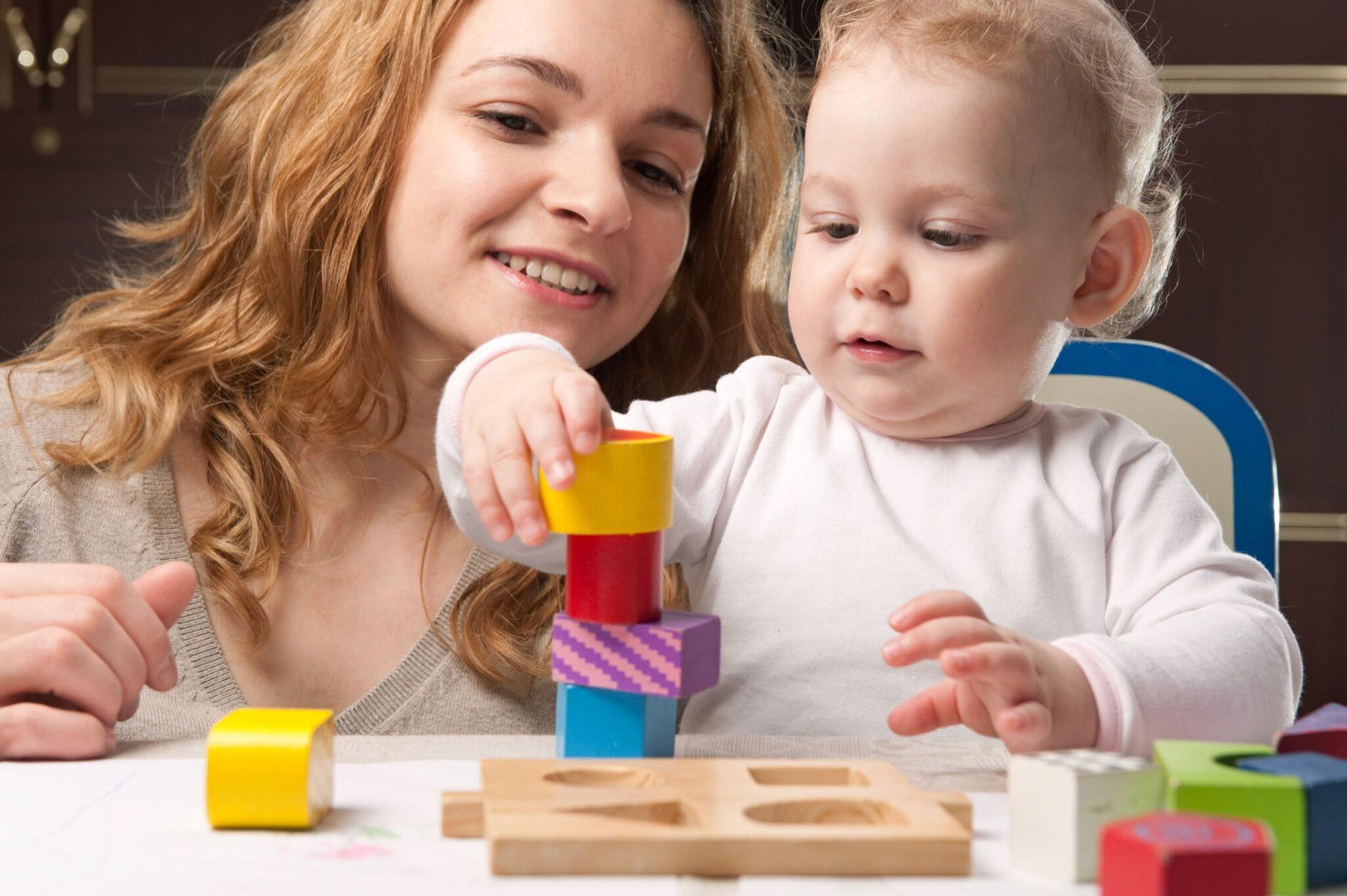 Baby building bricks with Nanny