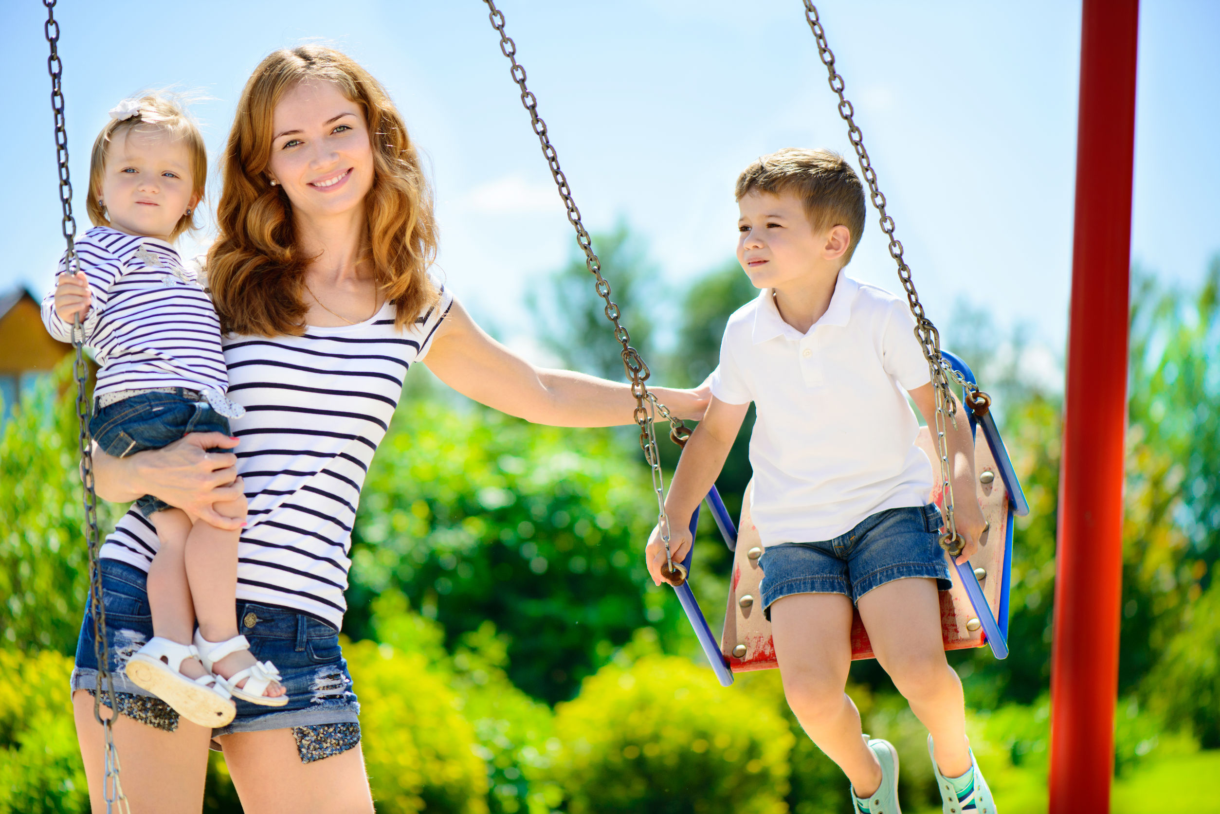 Happy nanny with 2 children at playground swings