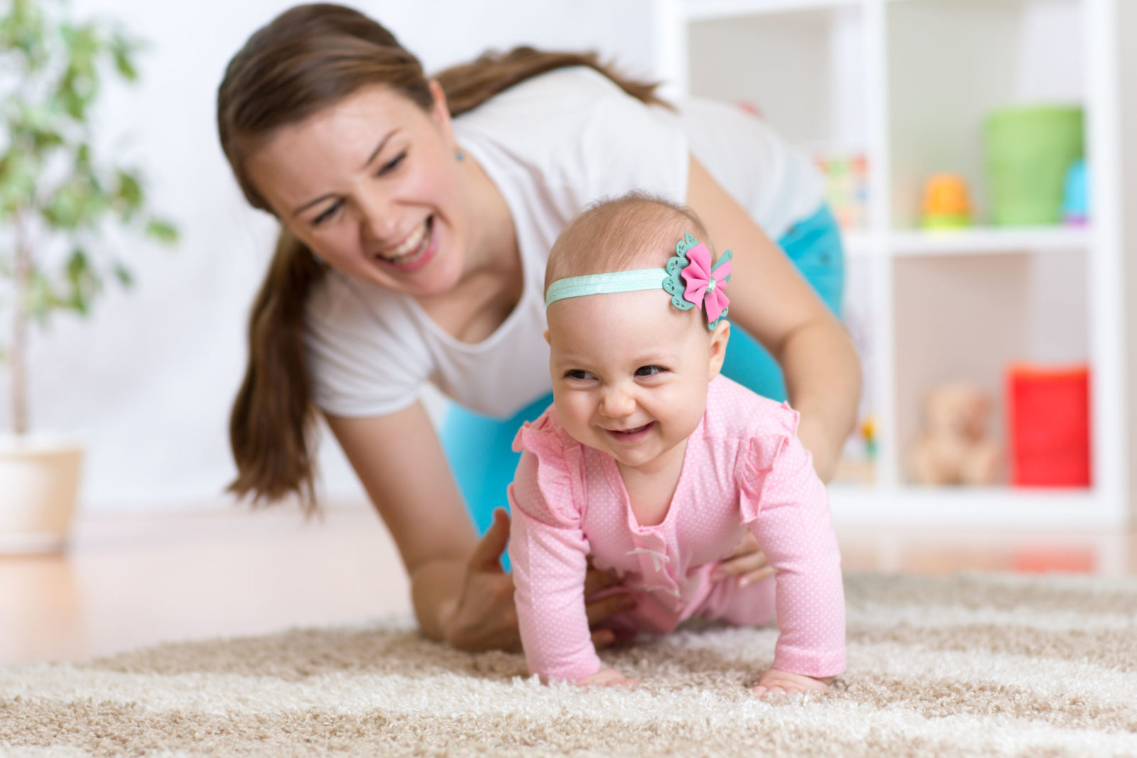 Nanny on the floor with baby in pink