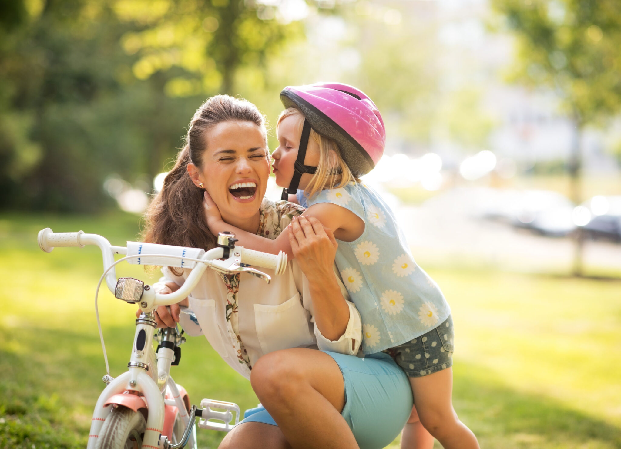 Happy Nanny and little girl cycling summertime