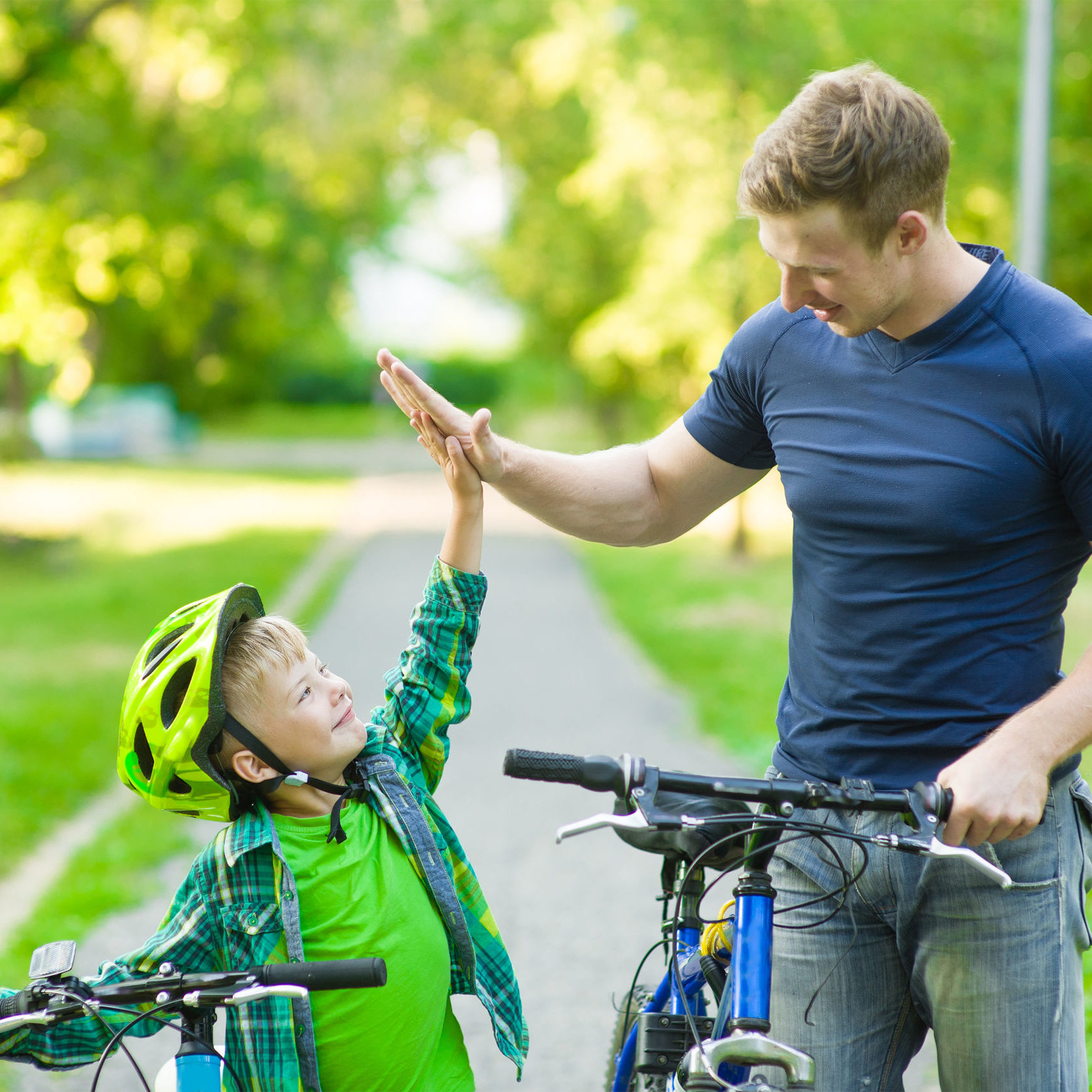 Young man and young boy give high five while cycling in the park